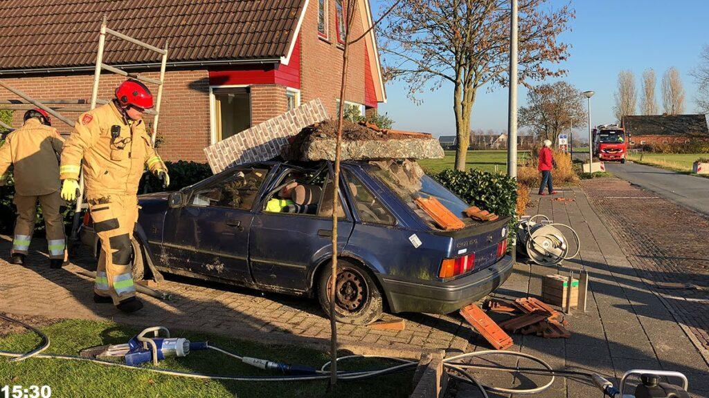 Foto van aardbevingsoefening in Zuidwolde. Op de foto staan brandweermannen om een auto die gesimuleerde schade heeft door de instorting van de gevel van een huis.