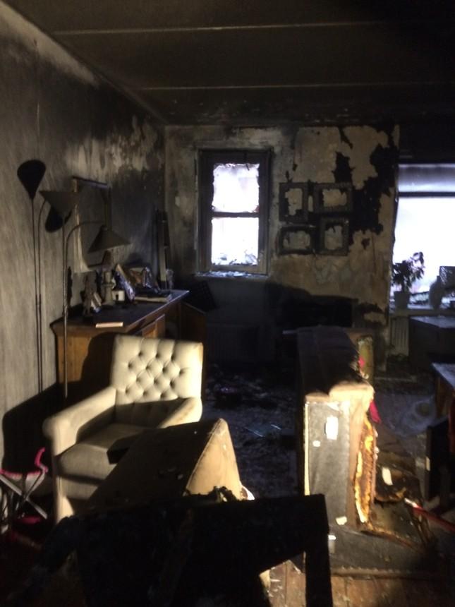 Woonkamer na de brand. Alles is zwart of door rook beshcadigd. Het plafond is zwart van de roet en de muren zijn duidelijk door de vlammen geraakt. Al het meubilair ligt om en is kapot. - foto: fam. Buurema