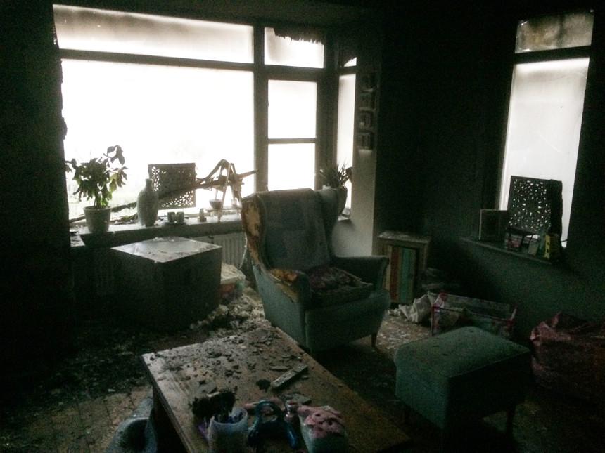 Woonkamer na de brand. Bijna alles isbeschadigd en zwart geblakerd. De tafel ligt vol met stukken verkoold interieur. De stoelen en banken zijn aangevreten door de vlammen. - Foto: Fam. Buurema