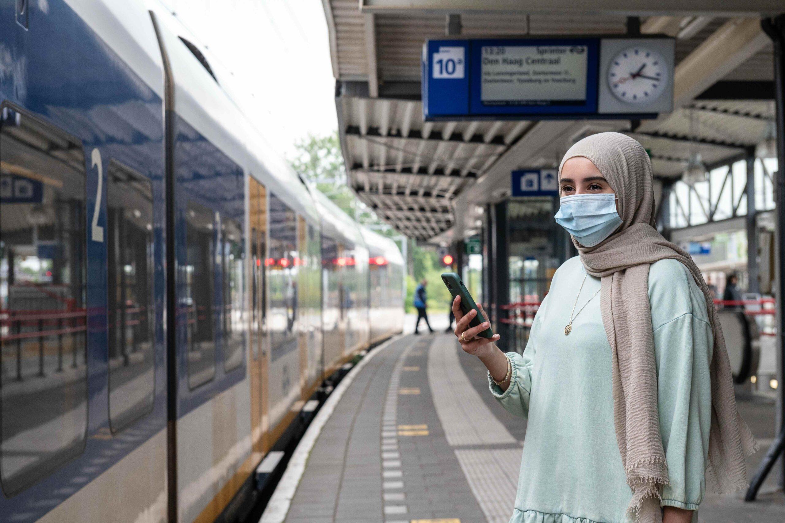 Reiziger op het perron voor de trein met een mondkapje voor.