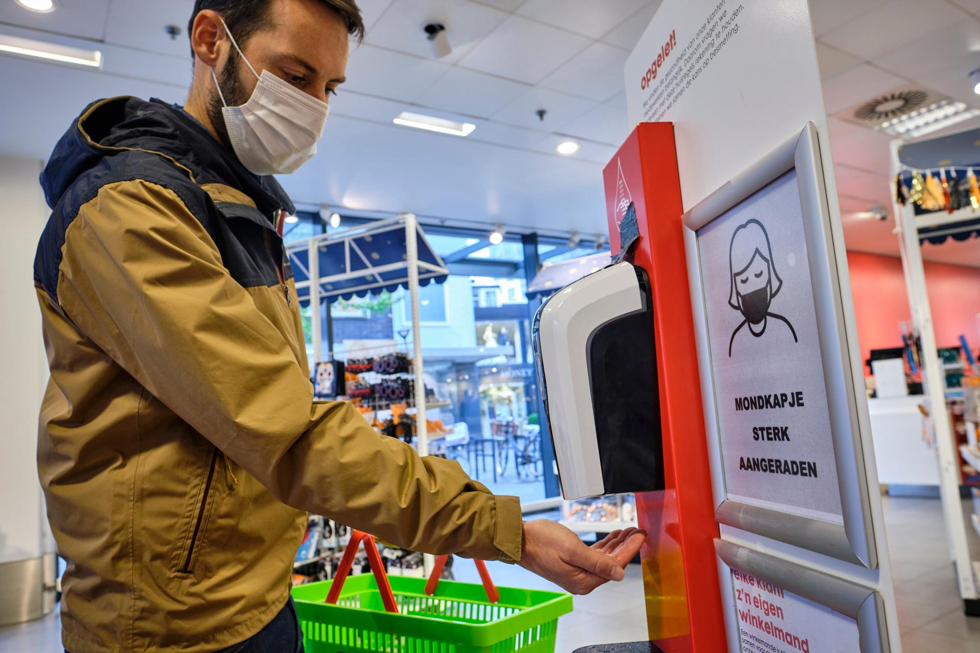 Shoppende klant ontsmet zijn handen in een winkel